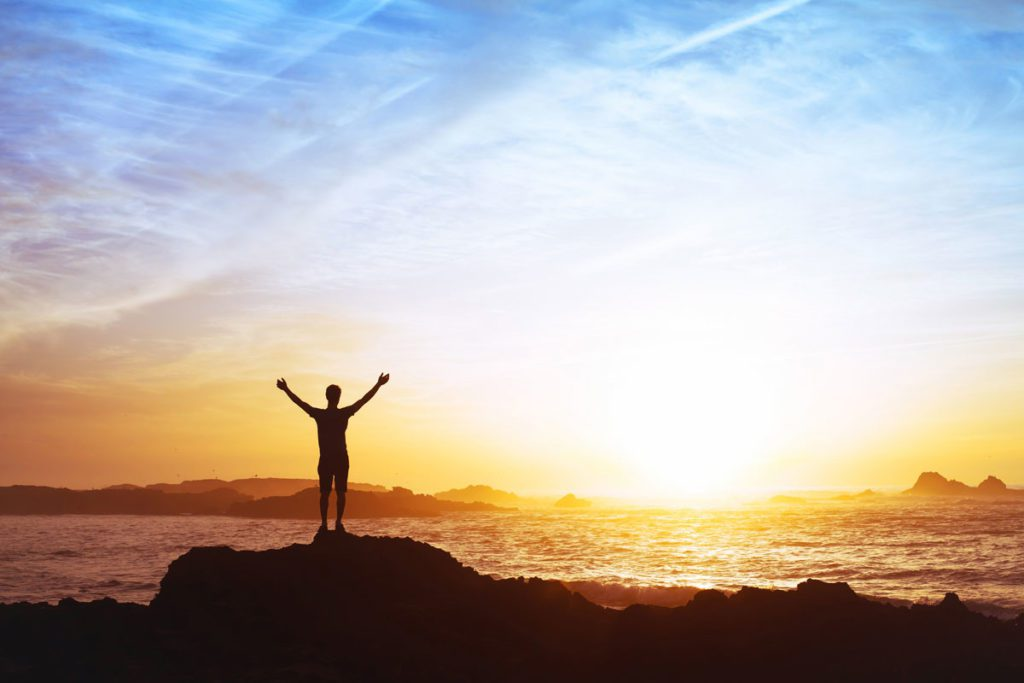 A picture of a young man with his arms raised in triumph facing a penetrating sunrise